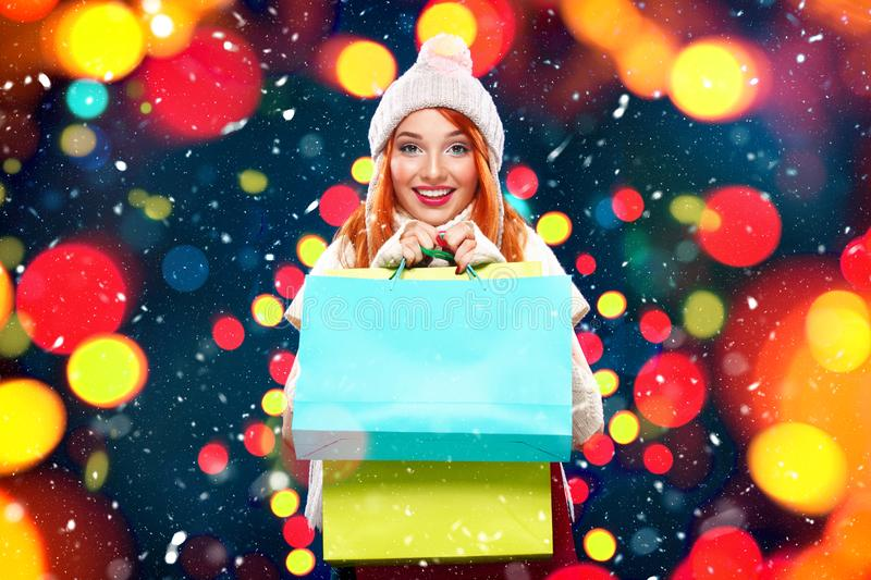 Christmas and New Year holidays.. Shopping woman holding color bags and on winter background with snow and lights in royalty free stock photo