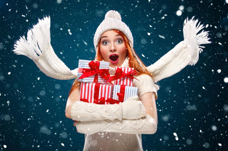Christmas and New Year holidays. Surprised woman holding gift boxes on winter background with snow in black friday. Sale stock photo