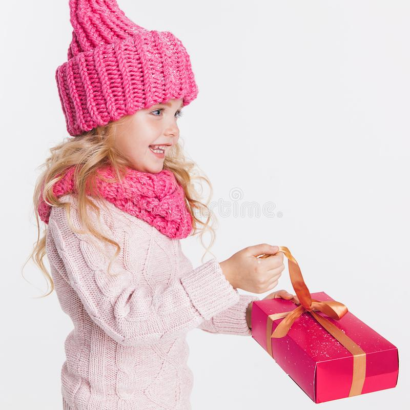 Christmas. New Year. Little girl holding present in winter clothes. Pink hat and scarf. Winter stock image