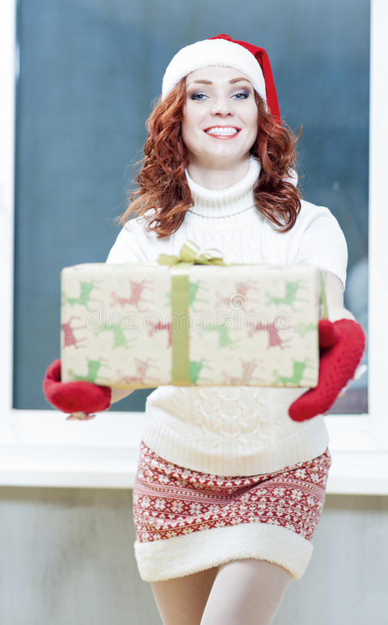 Christmas, New Year, X-Mas Concepts and Celebrations. Young Caucasian Santa Helper Girl Offers Big Present Box At Front. Posing royalty free stock image