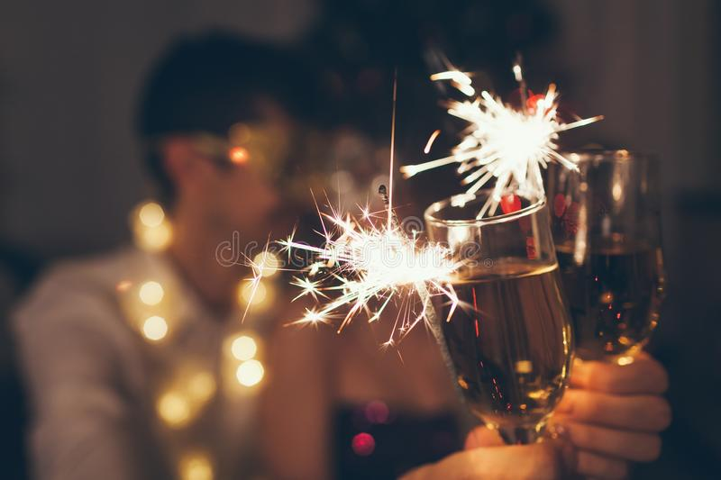 Christmas and New year party concept. Couple in love burning sparklers by illuminated Christmas tree with champagne stock images