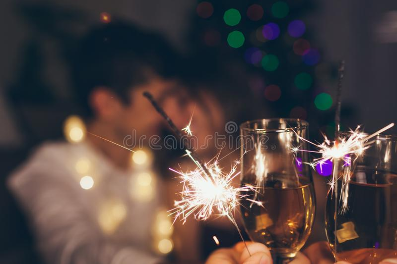 Christmas and New year party concept. Couple in love burning sparklers by illuminated Christmas tree with champagne stock image