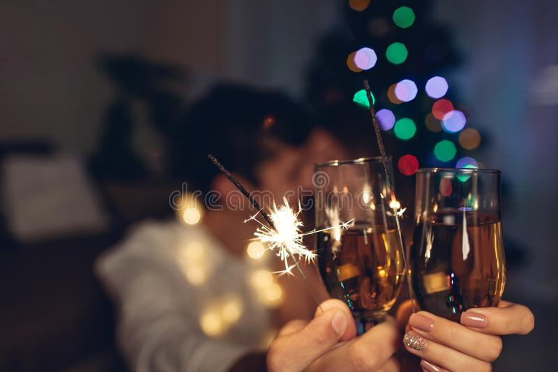 Christmas and New year party concept. Couple in love burning sparklers by illuminated Christmas tree with champagne royalty free stock image