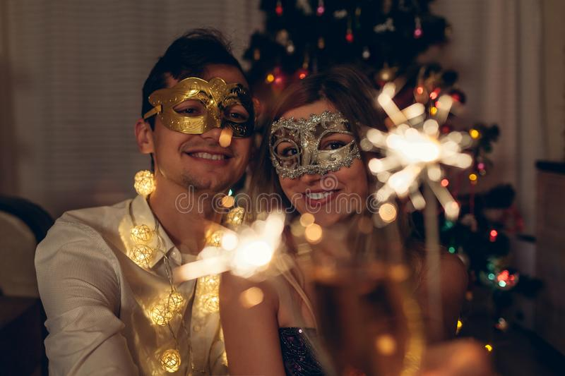 Christmas and New year party concept. Couple in love burning sparklers by illuminated Christmas tree with champagne royalty free stock photos