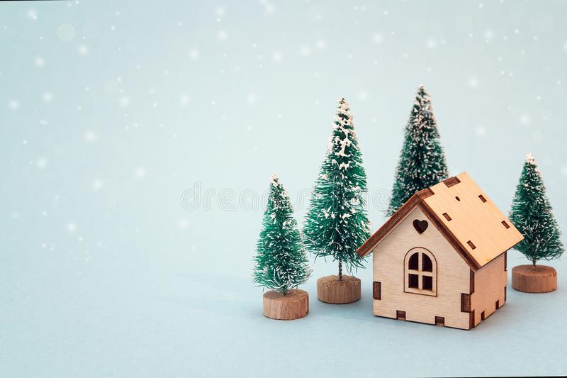 Christmas and New Year miniature house with fir trees on blue b stock image