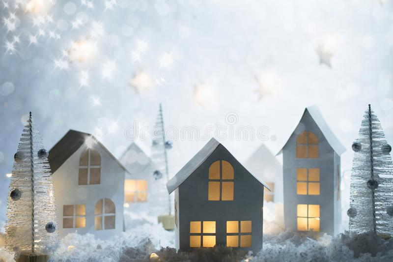 Christmas and New Year miniature magical house in the snow at night and bokeh city lights. Christmas decorations. stock image