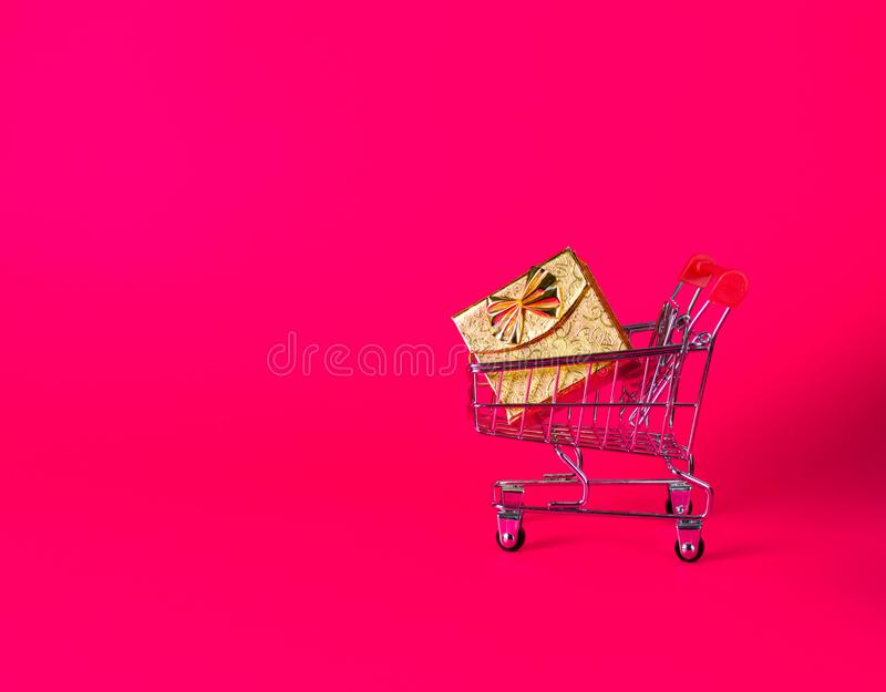 Christmas, new year mood on bright pink background. supermarket trolley with golden present royalty free stock image