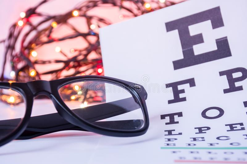 Christmas and New Year in ophthalmology optometry. Eyeglasses and ophthalmological table for visual acuity test in foreground with royalty free stock photo