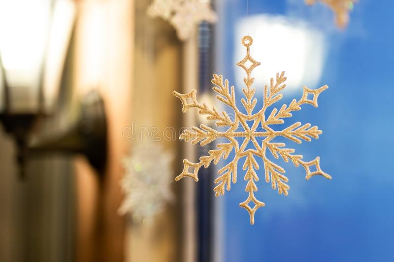 Christmas and new year ornament decoration snowlake handed near window with warm lamp lattern on background. Winter holidays card royalty free stock photo
