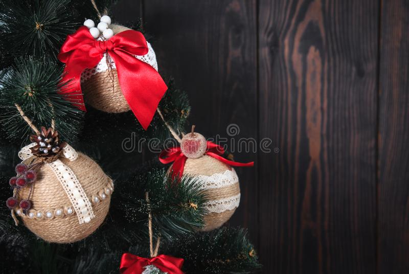 Christmas or New Year rustic wooden background with toy decorations and fur tree branch. stock photos