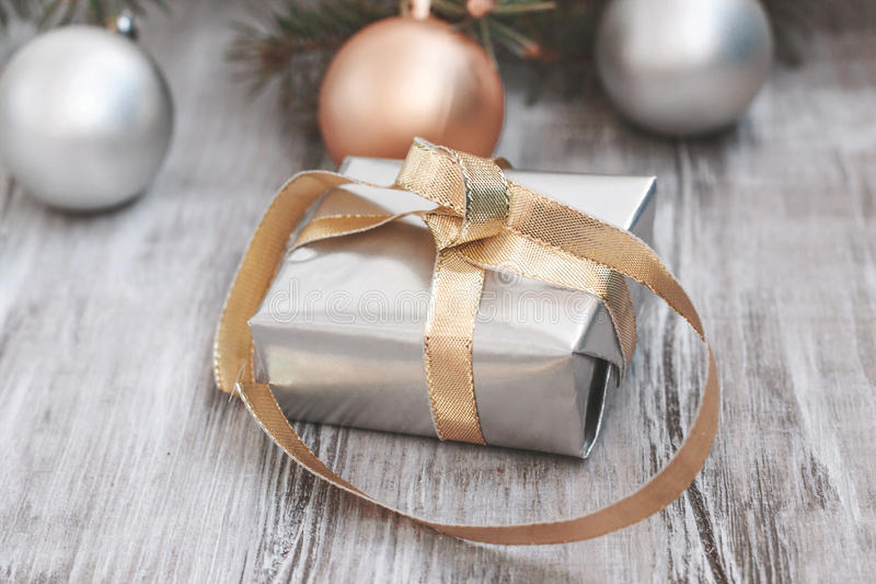 Christmas New Year`s composition. Gift in silver box with gold ribbon on the background of fir branches on a wooden table royalty free stock images