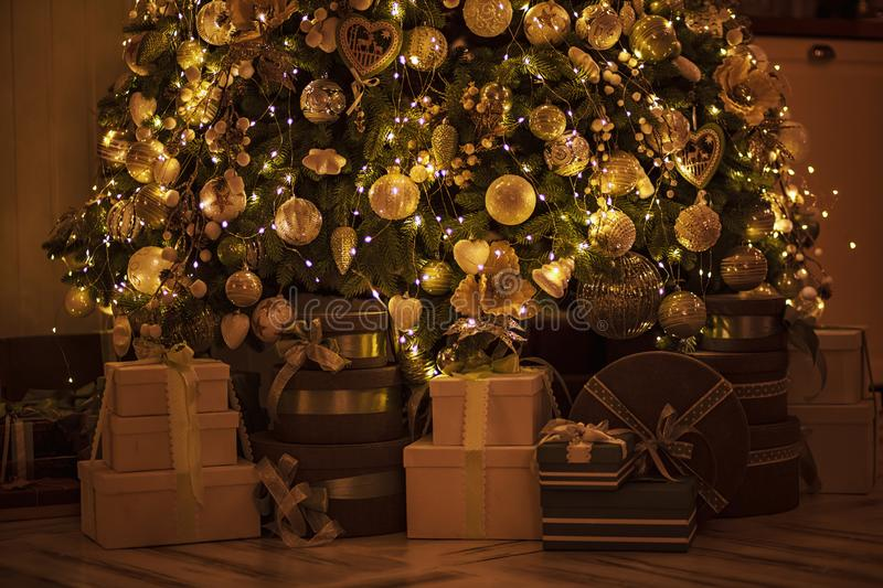 Christmas and New Year`s elegant decor tree with gifts. Beautiful decorated golden Christmas tree with present boxes in luxury cl stock photos