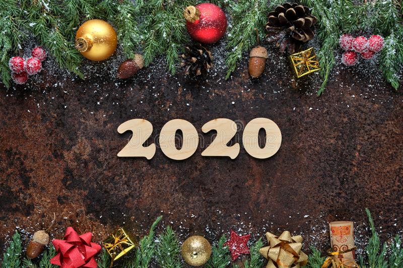 Christmas or New Year`s Eve festive background with wooden numbers 2020 and Christmas decorations on stone surface. Flat royalty free stock photos