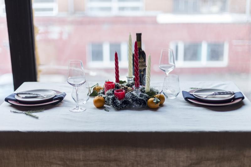Holiday festive table set with candle and wine. Christmas and New year`s festive table set with plates, candles, mandarins and wine at white table royalty free stock photo
