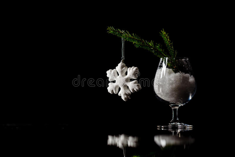 Christmas and New Year`s snow decorations on a black mirror reflection surface and dark bokeh lights background. Card template w stock photo