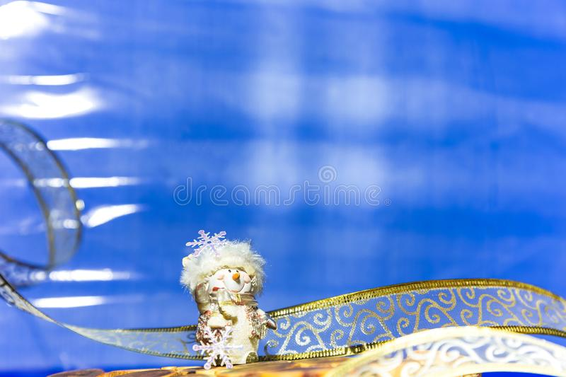 Christmas and New Year's winter festive background in blue with. A garland and a figure of a souvenir snowman with a copy space for writing the text of stock photos