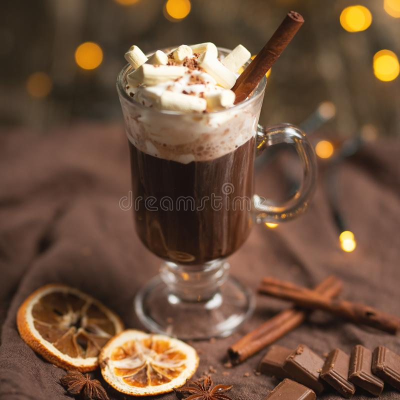 Christmas or New Year's winter hot chocolate with marshmallow in a dark mug, with chocolate, cinnamon and spices with a festive l. Ight garland, selective focus stock photography