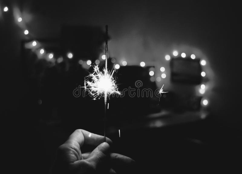 Sparkle in hand Christmas and New year decor home black and white background. Christmas and New year sparkle in hand black and white holiday background royalty free stock photos