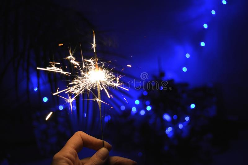 Sparkle in hand Christmas and New year decor home dark blue background. Christmas and New year sparkle in hand dark blue holiday background royalty free stock photos