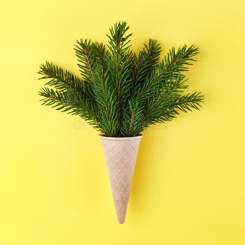 Christmas. New Year. Style minimalism. Christmas tree in ice cream cone on a yellow background. royalty free stock photos