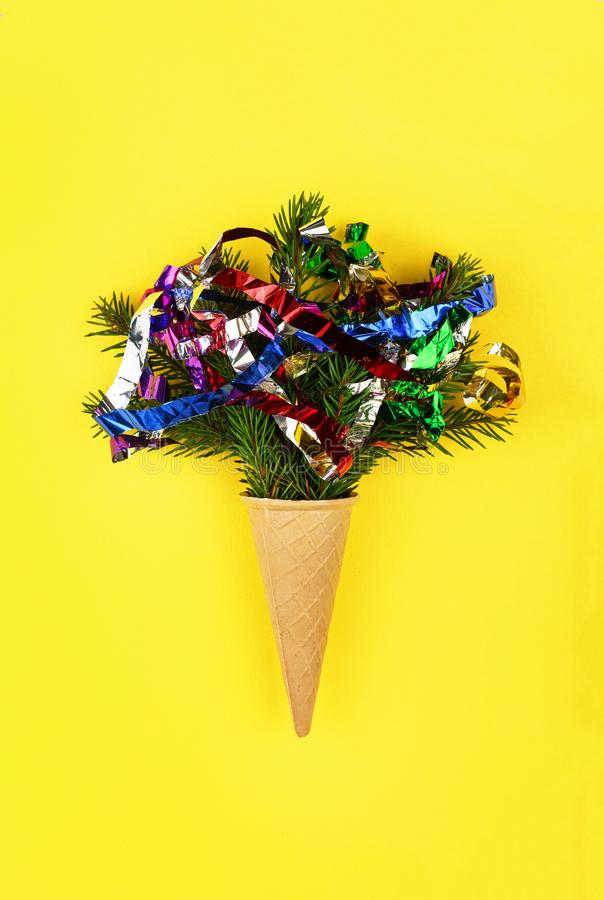 Christmas. New Year. Style minimalism. Christmas tree in ice cream cone on a yellow background stock photography