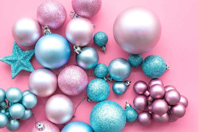 Christmas and New Year symbols. Toys for festive tree. Blue and pink balls and stars on pink background top view royalty free stock image