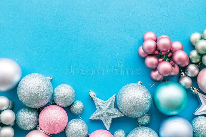 Christmas and New Year symbols. Toys for festive tree. Blue and pink balls and stars on blue background top view copy stock photos