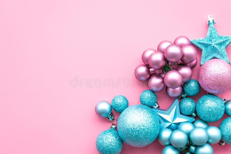 Christmas and New Year symbols. Toys for festive tree. Blue and pink balls and stars on pink background top view copy royalty free stock photos