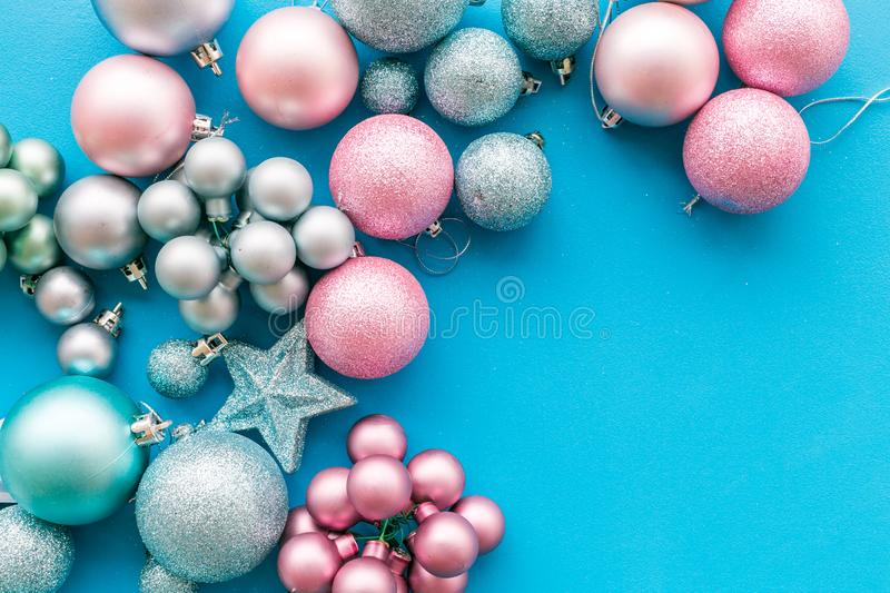 Christmas and New Year symbols. Toys for festive tree. Blue and pink balls and stars on blue background top view copy stock photography