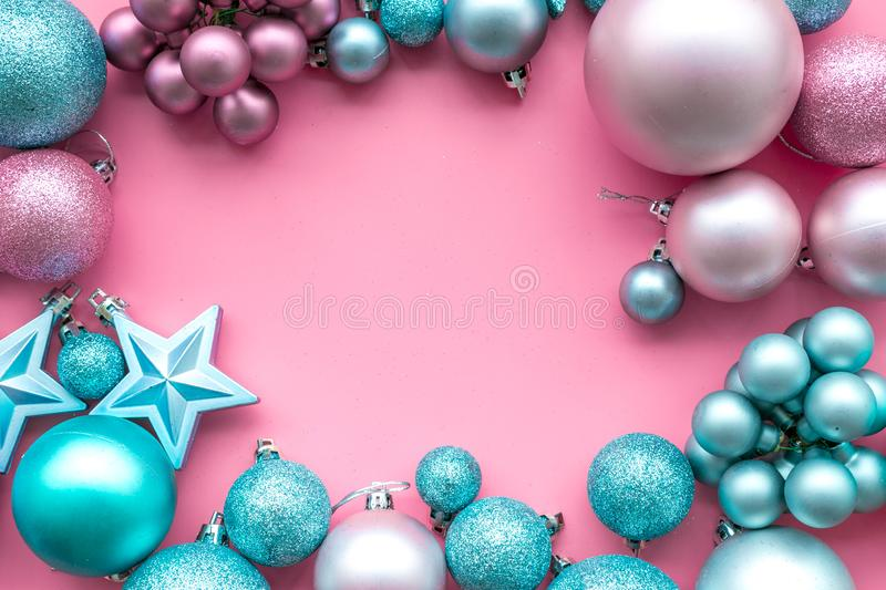 Christmas and New Year symbols. Toys for festive tree. Blue and pink balls and stars on pink background top view copy stock image