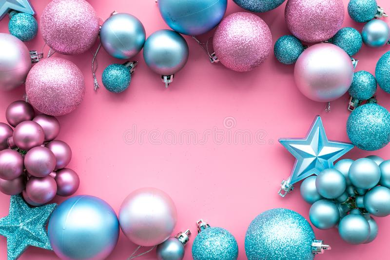 Christmas and New Year symbols. Toys for festive tree. Blue and pink balls and stars on pink background top view copy royalty free stock photo