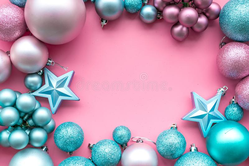 Christmas and New Year symbols. Toys for festive tree. Blue and pink balls and stars on pink background top view copy royalty free stock photography