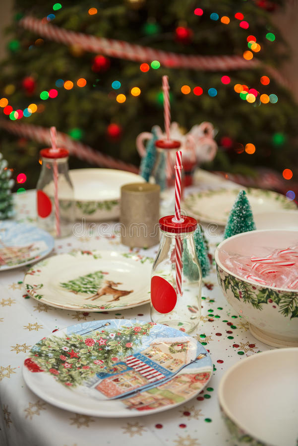 Christmas and New Year table place setting with empty Christmas plates with festive decorations bauble snowflake star bow ball pi stock photo