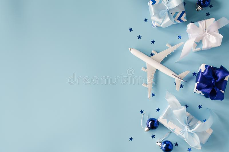 Christmas or New Year travel concept. Toy airplane with passports and gift boxes on blue background royalty free stock photography