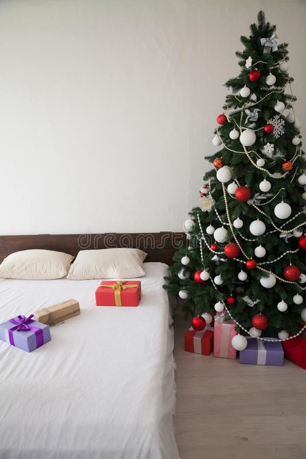 Christmas new year tree Interior bedroom and bed with gifts stock photography