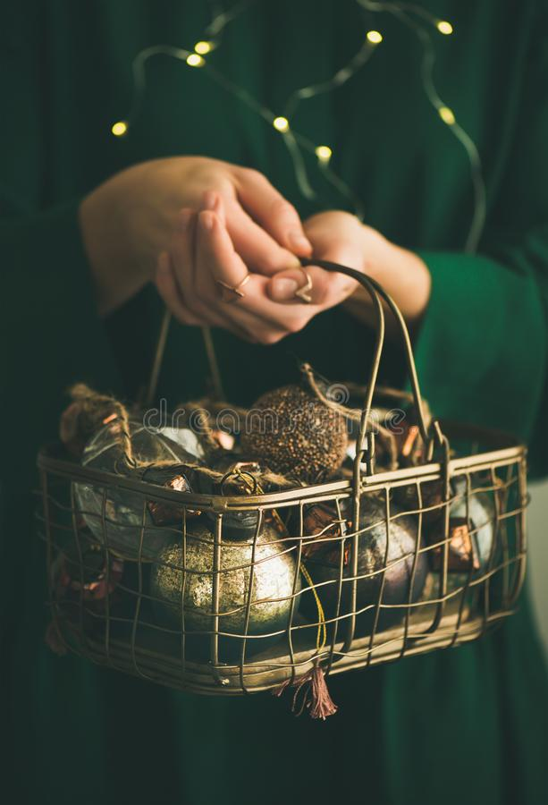Christmas, New Year tree vintage toys in wire basket. Wire basket full of Christmas or New Year tree vintage decoration toys in hands of woman in green festive royalty free stock image