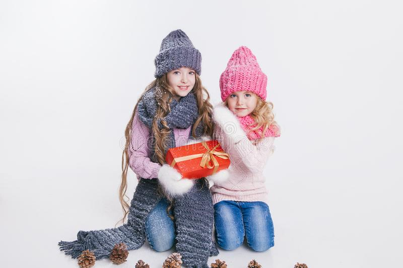 Christmas. New Year. Two little sisters holding present in winter clothes. Pink and grey hats and scarfs. Family. Winter.  stock photography