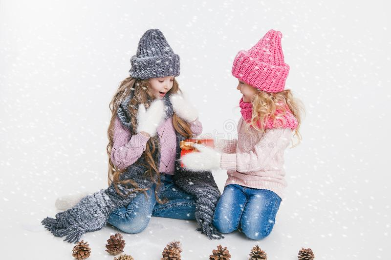 Christmas. New Year. Two little sisters holding present in winter clothes. Pink and grey hats and scarfs. Family. Winter. Congratulation stock photography