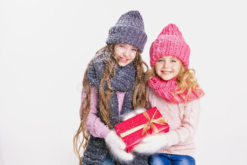 Christmas. New Year. Two little sisters holding present in winter clothes. Pink and grey hats and scarfs. Family. Winter royalty free stock image