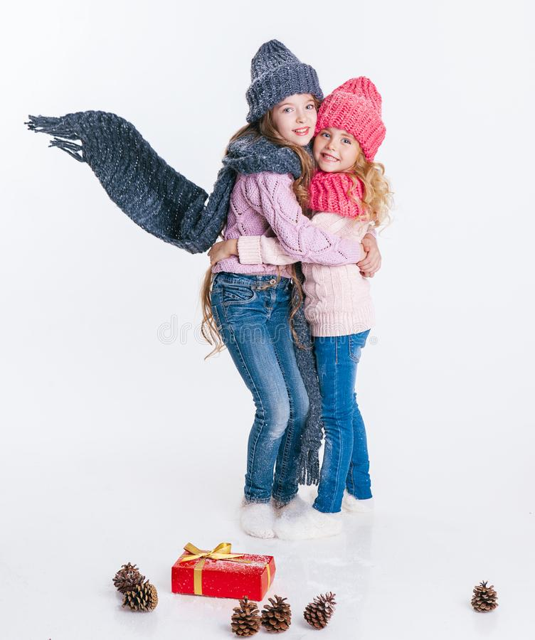 Christmas. New Year. Two little sisters holding present in winter clothes. Pink and grey hats and scarfs. Family. Winter stock photo