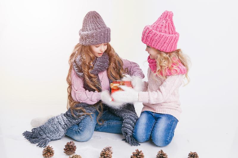 Christmas. New Year. Two little sisters holding present in winter clothes. Pink and grey hats and scarfs. Family. Winter.  stock photos