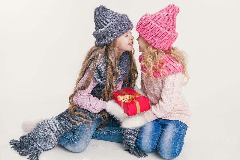 Christmas. New Year. Two little sisters holding present in winter clothes. Pink and grey hats and scarfs. Family. Winter. Congratulation royalty free stock photography