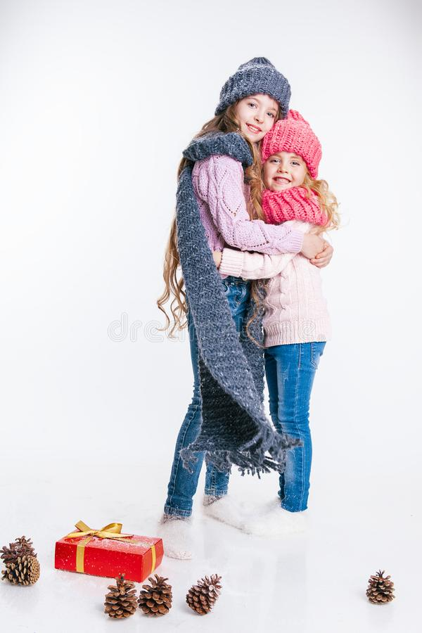 Christmas. New Year. Two little sisters holding present in winter clothes. Pink and grey hats and scarfs. Family. Winter stock image
