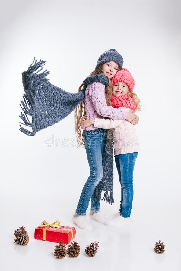 Christmas. New Year. Two little sisters holding present in winter clothes. Pink and grey hats and scarfs. Family. Winter royalty free stock photo