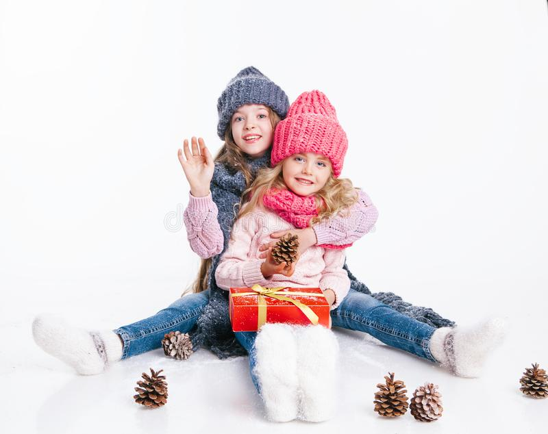 Christmas. New Year. Two little sisters holding present in winter clothes. Pink and grey hats and scarfs. Family. Winter royalty free stock images