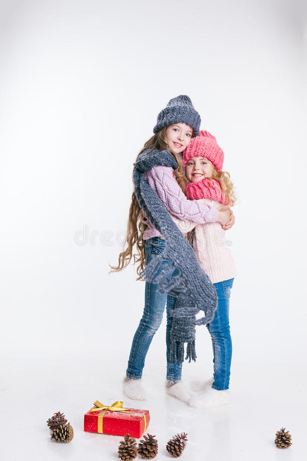 Christmas. New Year. Two little sisters holding present in winter clothes. Pink and grey hats and scarfs. Family. Winter. Christmas. New Year. Two little sisters royalty free stock photography