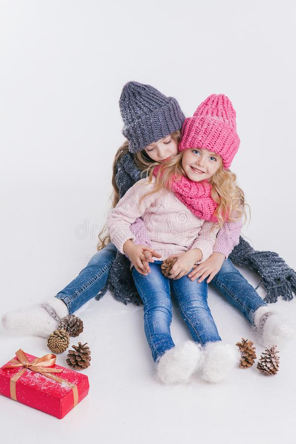 Christmas. New Year. Two little sisters siting near present in winter clothes. Pink and grey hats and scarfs. Family. Winter. Congratulation stock photography