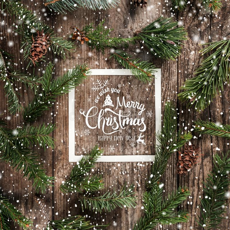 Christmas and New Year Typographical on wooden background with fir branches, frame of paper card note, pine cones and snowflakes. On wooden background. Xmas and vector illustration