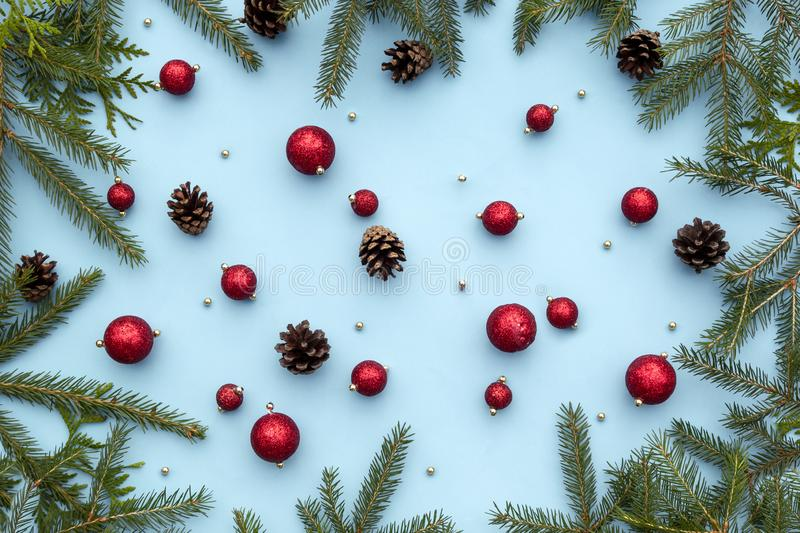 Christmas or new year winter composition. Red toys, spruce fir branches, pine cones, decorative Christmas ornaments on blue royalty free stock photo