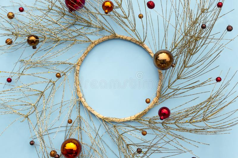 Christmas or new year winter composition. Round frame made of golden tree branches and red decorative Christmas ornaments on blue stock photo